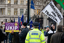 © Licensed to London News Pictures. 15/01/2019. London, UK. Pro-Brexit demonstrators wave a flag reading 'REMOANERS ARE TRAITORS' outside the Houses of Parliament, Westminster. Last week far-right demonstrators surround anti-Brexit MP Anna Soubry, calling her a 'nazi' and a 'traitor'. This evening, MPs are due to vote on British Prime Minister Theresa May's EU withdrawal deal, after the previous vote in December was postponed. Photo credit : Tom Nicholson/LNP