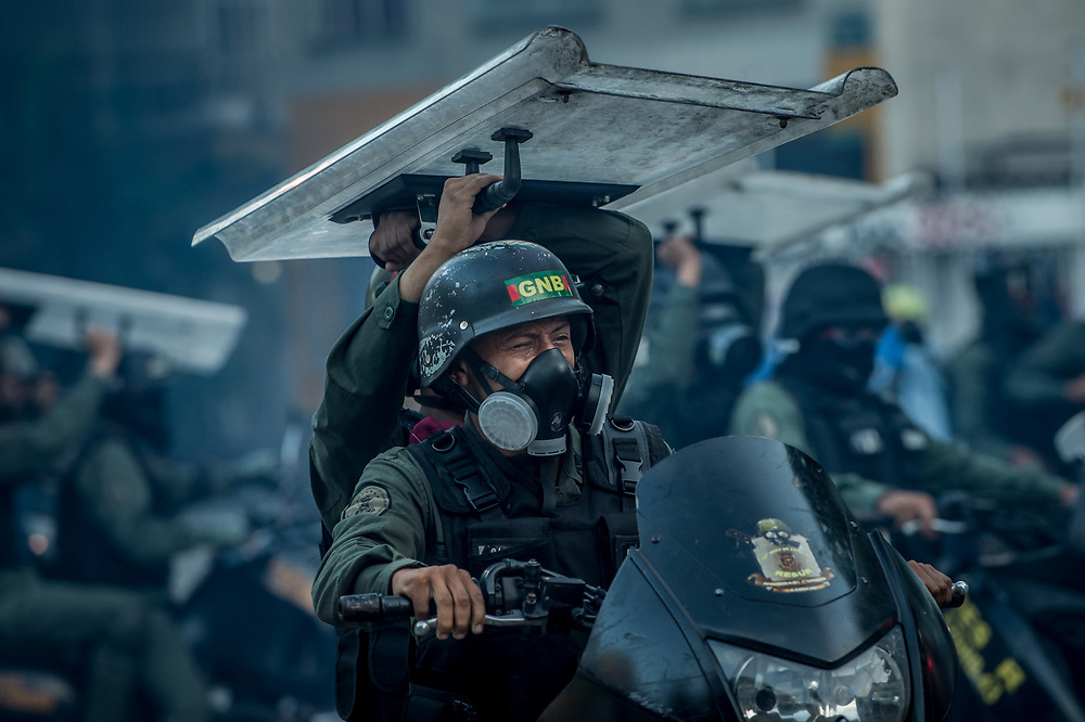 CARACAS, VENEZUELA - JULY 26, 2017: Soldiers chase protesters on motorcycles, one, overcome by tear gas - the other using a shield to protect them from rocks being thrown by protesters, during an anti-government protest to demand that the National Constituent Assembly election scheduled for Sunday, July 30th be cancelled. The political opposition called for a 48 hour national strike on July 26th and 27th, and for their supporters to close businesses, not go to work, and instead create barricades to block off their streets.  Opposition controlled areas of the country were completely shut down.  The strike was called as part of the opposition's civil resistance movement - that began on April 1st, to protest against the Socialist government's attempt to elect a new assembly that will have the power to re-write the constitution, and their opposition to the Socialist's continued threats to Venezuelan Democracy.  PHOTO: Meridith Kohut for The New York Times