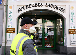 02 April 2020. Hesdin, Pas de Calais, France. <br /> Coronavirus - COVID-19 in Northern France.<br /> <br /> Easing restrictions on local markets. Security controls access to the local market which for the first time since government restrictions came into force has been permitted to re-open in Hesdin. The historical town has hosted a usually vibrant and bustling market since the Middle Ages. With stall holders limited and many suffering huge financial losses, those selling food today were happy to be back to work despite the ongoing risks posed by coronavirus.<br /> <br /> Shoppers, many wearing masks were mostly maintaining their social distancing with people happy to be out and able to meet and talk with other people. A lot of shoppers were elderly people who have been trapped in their homes for weeks. One shopper complained of 'la misère,' - the misery of this virus and being stuck in her home. <br /> <br /> Anyone leaving their home must carry with them an 'attestation,' in a effect a self administered permit to allow them out of the house. If stopped by the police, one must produce a valid permit along with identification papers. Failure to do so is punishable with heavy fines. Movement in France has been heavily restricted by the government and today's market re-opening was a brief return to normalcy for many able to escape the confines of their homes.<br /> <br /> Photo©; Charlie Varley/varleypix.com