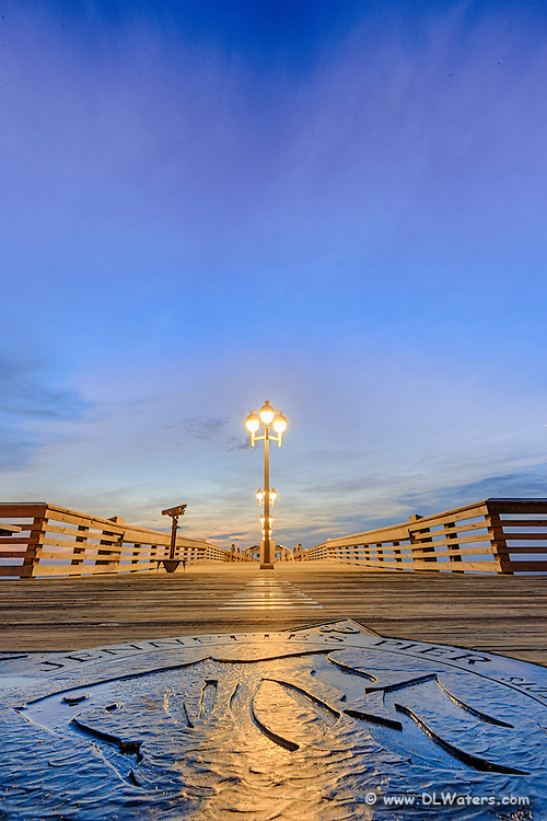 A close up wide angle shot of Jennette's Pier inlaid compass rose at twilight in Nags Head on the Outer Banks of NC.