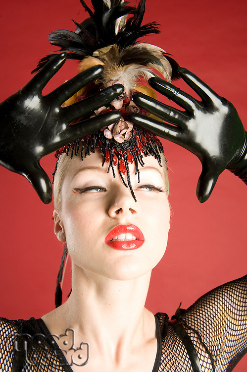Close-up of beautiful young woman wearing feather headwear and leather gloves looking away