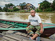 16 JUNE 2015 - SUNGAI KOLOK, THAILAND:  A boatman waits for a fare to take across the Kolok River to Malaysia. The border between Thailand and Malaysia in Sungai Kolok, Narathiwat, Thailand. Thai and Malaysians cross the border freely for shopping and family visits. The border here is the Kolok River (Sungai is the Malay word for river).        PHOTO BY JACK KURTZ