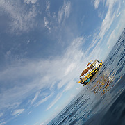The Reefer's Diving boat rests alone in calm waters as divers explore below the surface.