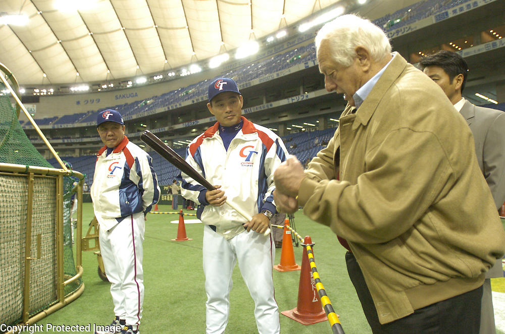 WBC Ambassador Tommy Lasorda (R) giving batting tips to Chinese Taipei Hitting Coach Ming-Tsu Lu (C) while manager Hua-Wei Lin (L) looks on during pregame warm-ups before the start of Game 5 against Team China in the World Baseball Classic at Tokyo Dome, Tokyo, Japan.