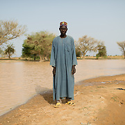 Lokoyo Namata is chief of the village of Gadirga in the Commune of Soukoukoutan in the Dosso Region of Niger. He is pictured next to a seasonal pool that is used for watering animals, laundry and bathing. 23 July 2013