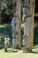 A women with a child photographing an Eagle, Killer Whale and Grizzly Bear totems at SGang Gwaay Lingagaay National Historic Site on Haida Gwaii, British Columbia, Canada. A UNESCO World Heritage Site protecting a Northwest Coast First Nations village site.