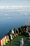 "Eco-tourists and photographers on the bow of the expedition vessle ""Polar Star"" watching for exciting events in the ice off north-western Spitsbergen"