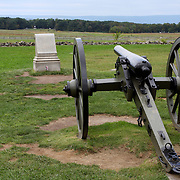 Union army cannon overlooking the fields of Pickett's Charge. The monument in front of the cannon marks where Confederate Brigadier General Lewis Armistead fell mortally wounded after his men made the furthest penetration of the Union line in the area called the Angle. Gettysburg.