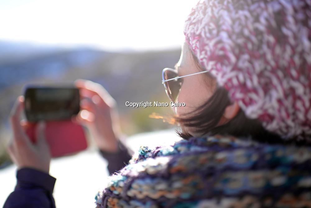 Young woman takes photos using mobile phone in winter environment