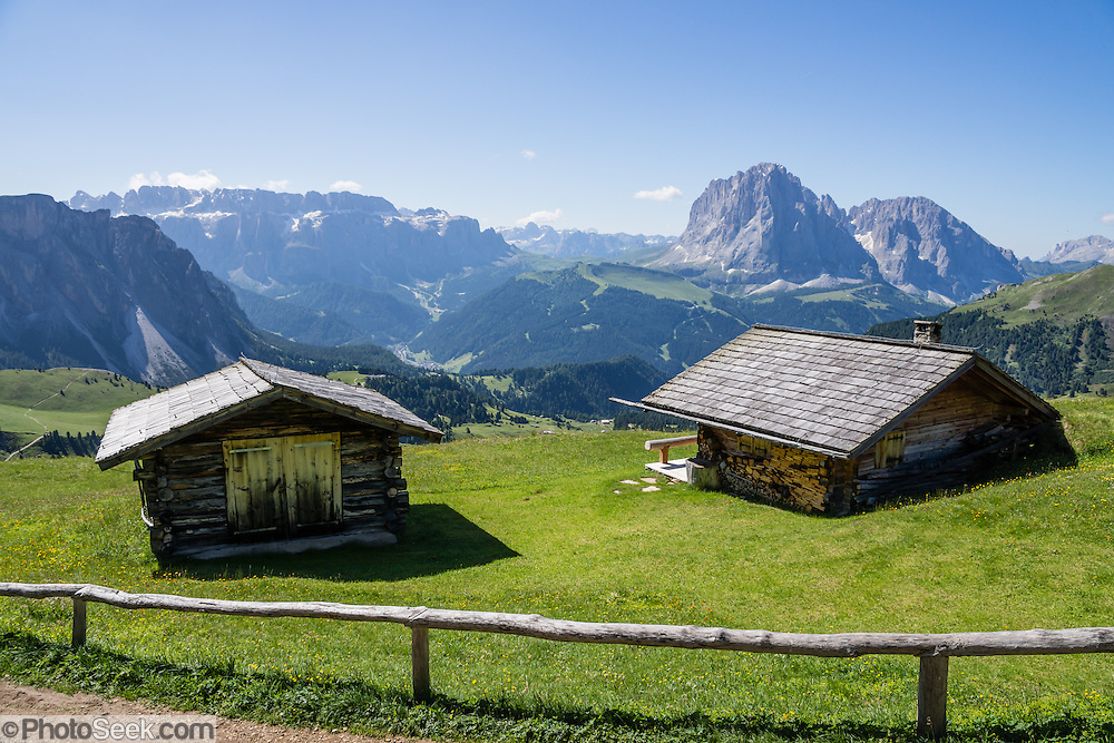 Walk in beautiful Alpe di Seceda by wooden malga (or singular malghe: a herders hut), above St. Christina and Ortisei, in Val Gardena, in South Tyrol, the Dolomites, Italy, Europe. In the distance on left is the wide plateau of the Sella Group and on right is Langkofel Group (Sassolungo, 3181 meters/10,436 feet, above Ciampinoi and Alpe di Suisi). The beautiful ski resort of Selva di Val Gardena (German: Wolkenstein in Gröden; Ladin: Sëlva Gherdëine) makes a great hiking base in the Trentino-Alto Adige/Südtirol (South Tyrol) region of Italy. For our favorite hike in the Dolomiti, start from Selva with the first morning bus to Ortisei, take the Seceda lift, admire great views up at the cross on the edge of Val di Funes (Villnöss), then walk 12 miles (2000 feet up, 5000 feet down) via the steep pass Furcela Forces De Sieles (Forcella Forces de Sielles) to beautiful Vallunga (trail #2 to 16), finishing where you started in Selva. The hike traverses the Geisler/Odle and Puez Groups from verdant pastures to alpine wonders, all preserved in a vast Nature Park: Parco Naturale Puez-Odle (German: Naturpark Puez-Geisler; Ladin: Parch Natural Pöz-Odles). UNESCO honored the Dolomites as a natural World Heritage Site in 2009.
