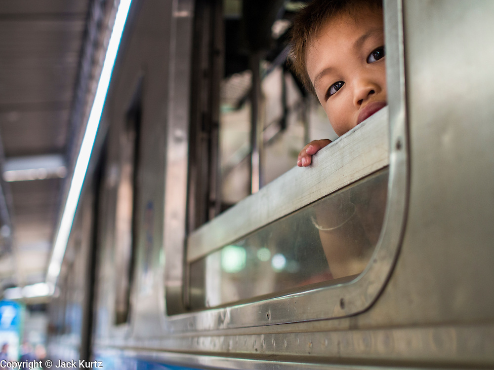 16 APRIL 2014 - BANGKOK, THAILAND: A boy waits for his train to pull out of Hua Lamphong Railway Station, the main train station in Bangkok. Thai highways, trains and buses were packed Wednesday as Thais started returning home after the long Songkran break. Songkran is normally three days long but this year many Thais had at least an extra day off because the holiday started on Sunday, so many Thais started traveling on Friday of last week.    PHOTO BY JACK KURTZ