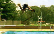 Neshaminy State Park, Bensalem, PA.-.Tyron Loving, 12, of Trenton, NJ. dives through the air, on his way into the pool at Neshaminy State Park while trying to keep cool on Thursday afternoon. 4of4