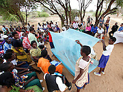Children from the Ruvu Lutheran Parish in the Kilimanjaro District in northeast Tanzania, demonstrate how to properly use a bed net during a performance about malaria prevention, Saturday, Aug. 11, 2012. The United Nations Foundation supports faith based partnerships such as the Lutheran Malaria Initiative, which helps connect United States congregations with worshippers across Africa to raise awareness of malaria. (Stuart Ramson/Insider Images for UN Foundation)