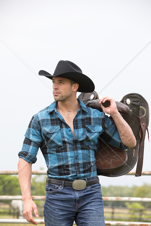 rugged cowboy with a saddle over his shoulder