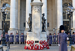 © Licensed to London News Pictures. 11/11/2012. City of London, UK The war memorial outside the Stock exchange and the Bank of England, People gather at a service of remembrance to remember those killed in action during conflict fighting for the UK. The Stock Exchange, today 11 November 2012. Both Armistice Day and Remembrance Sunday fall of the same day this year. Photo credit : Stephen Simpson/LNP