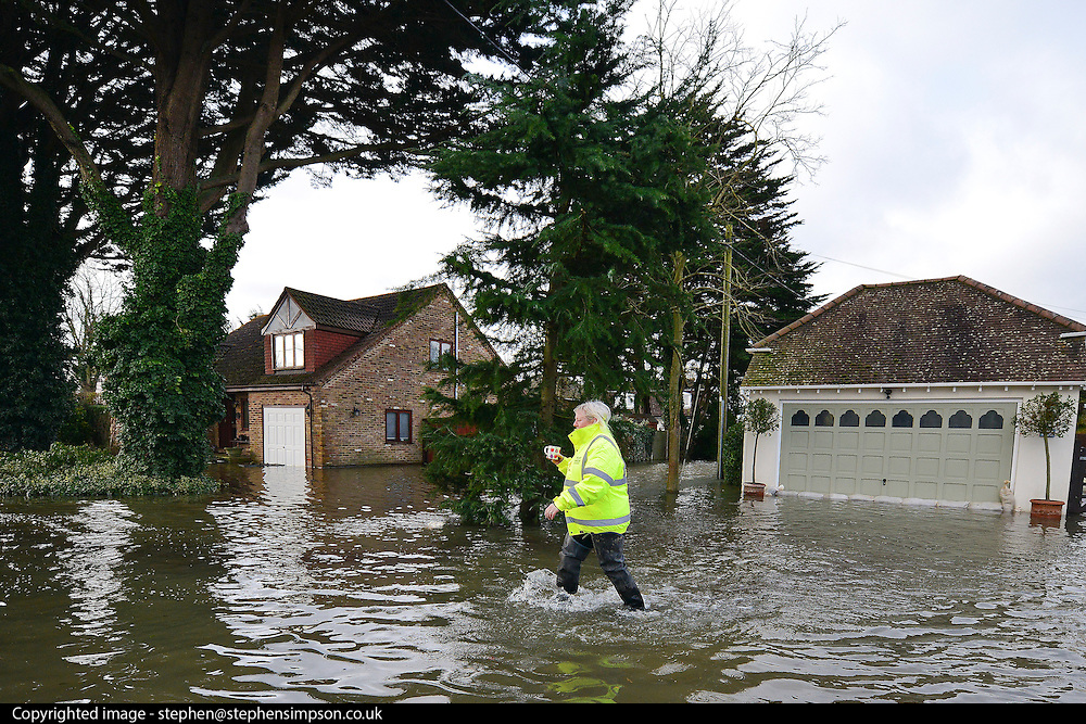 © Licensed to London News Pictures. 09/02/2014. Wraysbury, UK. A flood warden makes her way through the floodwater.  Flooding in Wraysbury in Berkshire today 9th February 2014 after the River Thames burst its banks. Photo credit : Stephen Simpson/LNP