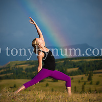 dramatic rainbow over woman doing yoga in a mountain medow
