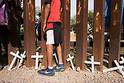 A boy looks through the U.S.-Mexico border wall in Nogales, Sonora, Mexico with crosses left for migrants who lost their lives at his feet during an immigration-focused rally on November 12, 2017. This demonstration was part of a weekend of actions called the SOA Watch Border Encuentro held along the Arizona, U.S.-Sonora, Mexico border region focused on immigrant rights, the demilitarization of the border, and other human rights issues.
