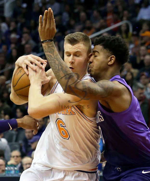 New York Knicks forward Kristaps Porzingis (6) collides with Phoenix Suns forward Marquese Chriss in the first half during an NBA basketball game, Friday, Jan. 26, 2018, in Phoenix. (AP Photo/Rick Scuteri)