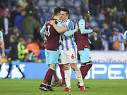 Aaron Cresswell of West Ham United and Huddersfield Town's Jonathan Hogg embrace at full time  during the Premier League match between Huddersfield Town and West Ham United at the John Smiths Stadium, Huddersfield, England on 13 January 2018. Photo by Paul Thompson.