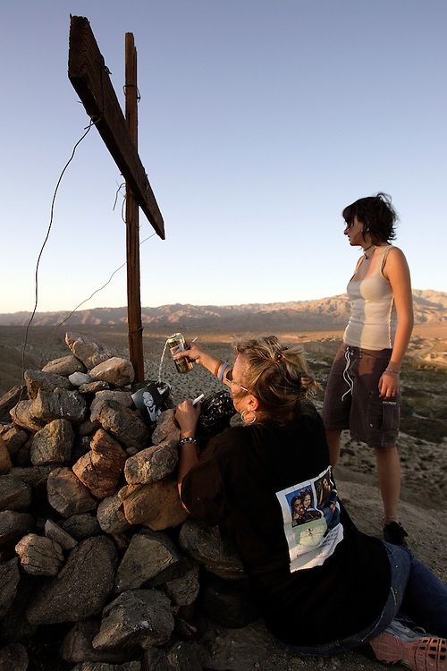 """PALM DESERT, CA, OCTOBER 21, 2006: Louisa Prudhomme, mother of Anthony Prudhomme who was murdered in a hate crime by Latino gang members in Highland Park, CA, regularly visits the site where she buried her son's ashes. Located about 150 miles from her home, Anthony's ashes lay buried beneath a cross high atop a hill overlooking the Coachella Nature Preserve. This was a favorite spot for Anthony. Louisa """"honored"""" Anthony by pouring a can of Anthony's favorite beer, Miller, on his ashes.......Photograph by Todd Bigelow/Aurora). ..PALM DESERT, CA, OCTOBER 21, 2006: Louisa Prudhomme, mother of Anthony Prudhomme who was the murder victim in a hate crime by Latino gang members in Highland Park, CA, regularly visits the site where she buried her son's ashes. Located about 150 miles from her home, Anthony's ashes lay buried beneath a cross high atop a hill overlooking the Coachella Nature Preserve. This was a favorite spot for Anthony. Family, including Anthony's brother, Michael and cousin, Carina Powell, and close friends also visited the site with Louisa who carried her favorite photo of her son to the site. Louisa also """"honored"""" Anthony by drinking his favorite and last drink, a can of Miller beer.......Photograph by Todd Bigelow/Aurora). .."""