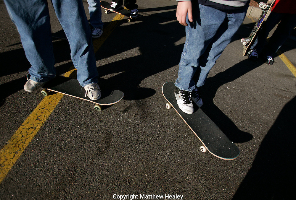 A group of teenage skate boarders hang out in the parking lot of a shopping mall.  Photo by Matthew Healey