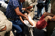 14 SEPTEMBER 2003 - CANCUN, QUINTANA ROO, MEXICO:  Mexican riot police detain an anti-globalization protestor in the hotel zone of Cancun, Mexico, during protests against the World Trade Organization during the WTO ministerial meetings taking place in the convention center in Cancun. Thousands of anti-globalization protestors have come to Cancun to demonstrate against the trade body. Mexican police have restricted most of the protestors to downtown Cancun, about five miles from the convention center. Small groups of protestors have been able to get into the hotel zone by posing as tourists. PHOTO BY JACK KURTZ