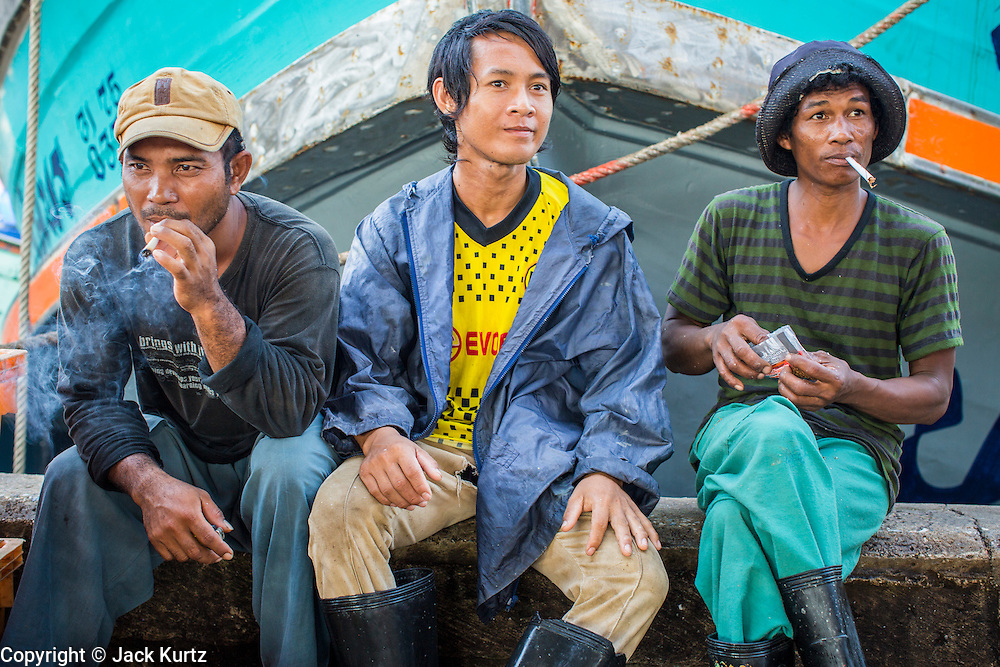 30 OCTOBER 2012 - PATTANI, PATTANI, THAILAND:   Burmese men who crew a Thai fishing trawler relax in the port of Pattani, province of Pattani, Thailand. Thailand's fishing industry relies on immigrant workers, mostly from Myanmar but also Laos and Cambodia. There have been allegations of worker abuse, including charges that workers are held in slave labor like conditions.  There are hundreds of thousands of immigrant workers in the Thai fishing industry. Most are from Myanmar (Burma) but there are also Cambodian and Laotian workers in the industry.    PHOTO BY JACK KURTZ