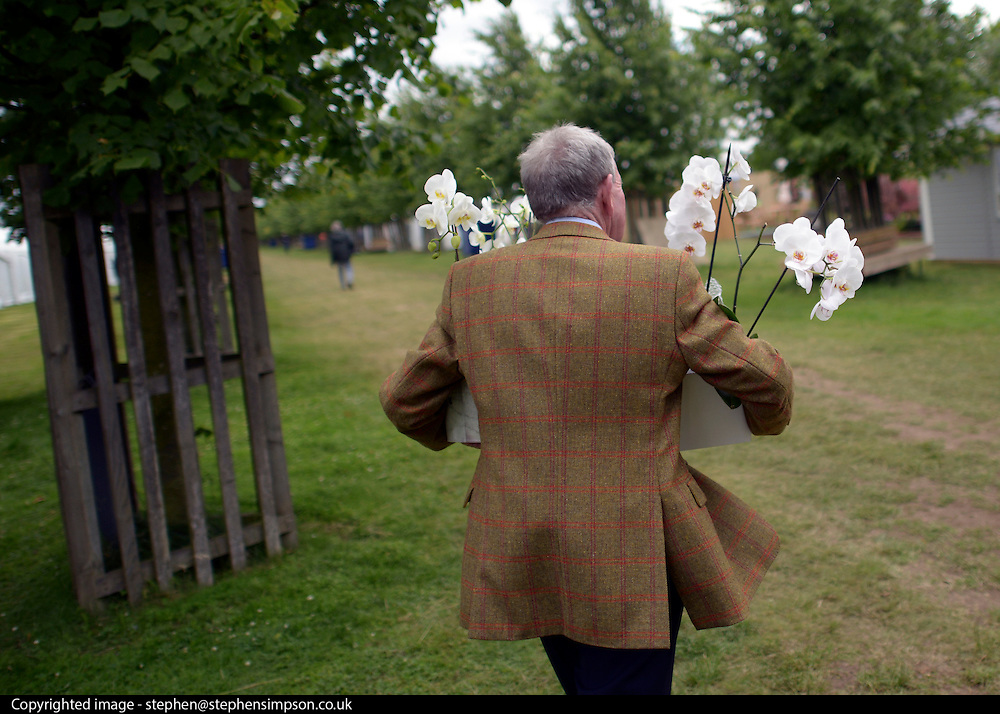 © Licensed to London News Pictures. 02/07/2012. East Molesey, UK A man carries orchids. The RHS Hampton Court Palace Flower Show 2012. The show runs 3-8 July, 2012. Photo credit : Stephen Simpson/LNP