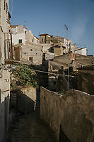 "SUTERA, ITALY - 8 JANUARY 2018: A view of the historical center of Sutera, Italy, on January 8th 2018.<br /> <br /> Sutera is an ancient town plastered onto the side of an enormous monolithic rock, topped with a convent, in the middle of the western half of Sicily, about 90 minutes by car south of the Sicilian capital Palermo<br /> Its population fell from 5,000 in 1970 to 1,500 today. In the past 3 years its population has surged  after the local mayor agreed to take in some of the thousands of migrants that have made the dangerous journey from Africa to the Sicily.<br /> <br /> ""Sutera was disappearing,"" says mayor Giuseppe Grizzanti. ""Italians, bound for Germany or England, packed up and left their homes empty. The deaths of inhabitants greatly outnumbered births. Now, thanks to the refugees, we have a chance to revive the city.""<br />  Through an Italian state-funded project called SPRAR (Protection System for Refugees and Asylum Seekers), which in turn is co-funded by the European Union's Fund for the Integration of non-EU Immigrants, Sutera was given financial and resettlement assistance that was co-ordinated by a local non-profit organization called Girasoli (Sunflowers). Girasoli organizes everything from housing and medical care to Italian lessons and psychological counselling for the new settlers.<br /> The school appears to have been the biggest beneficiary of the refugees' arrival, which was kept open thanks to the migrants.<br /> Nunzio Vittarello, the coordinator of the E.U. project working for the NGO ""I Girasoli"" says that there are 50 families in Sutera at the moment."