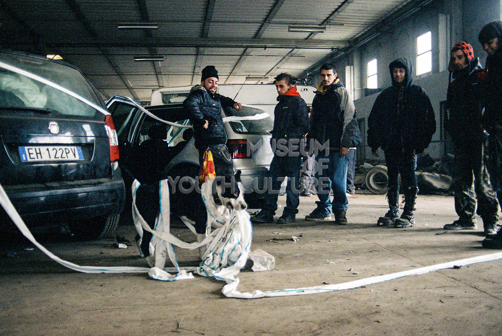 A group of men with a dog tangled in rags at Napoli NYE Tek, a New Year's Eve party in Naples, Italy, December 2014