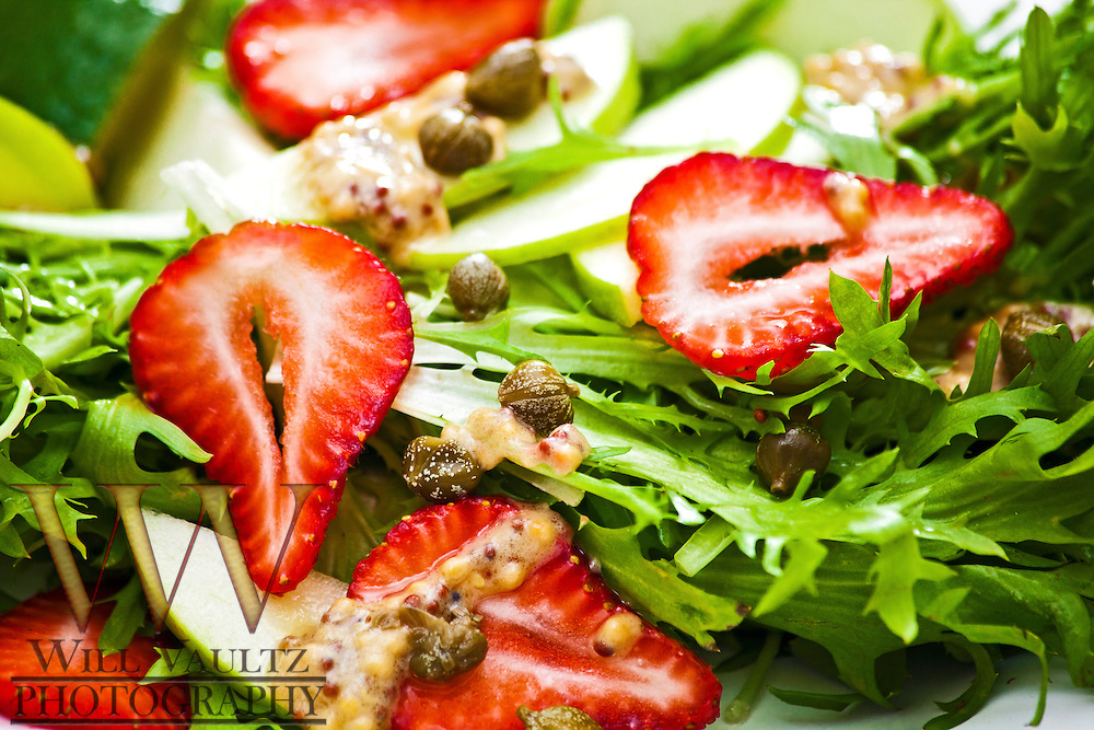 A simple salad with strawberries, Green apples, Capers on a bed of chicory with mustard vinaigrette drizzled over-the-top.