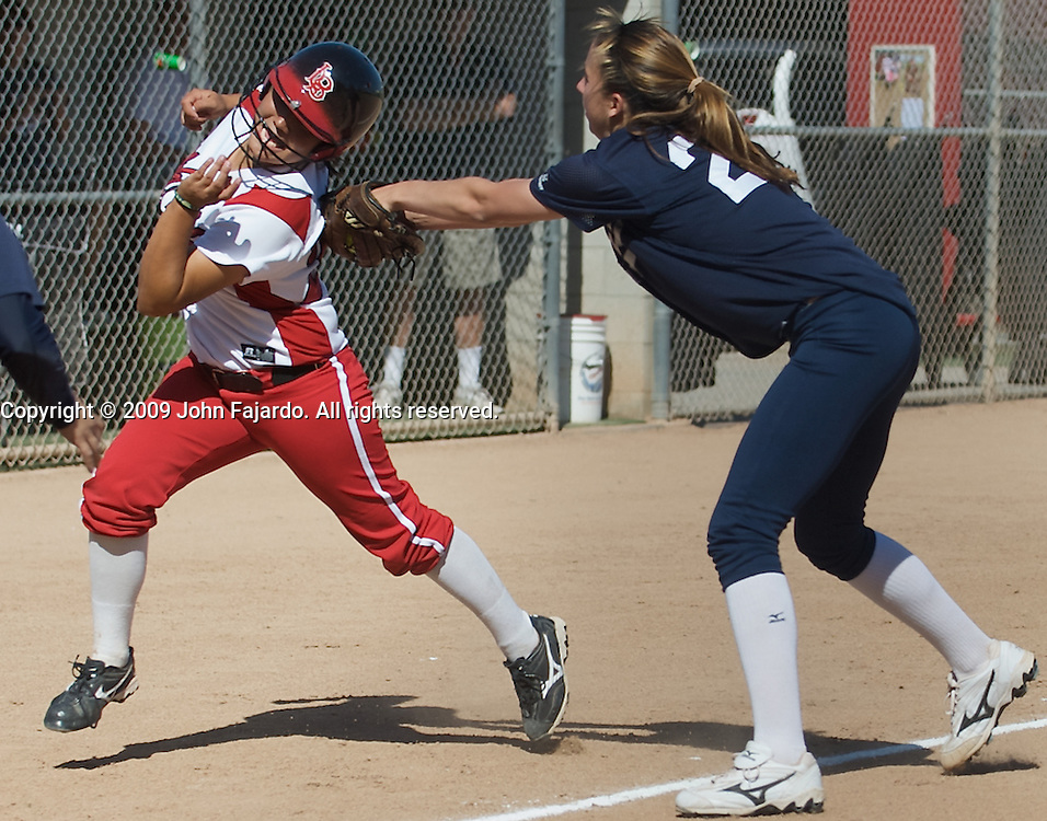 LBCC baserunner Christine Gonzalez twists to avoid the tag from Kaycee Wilke in the game against South Coast Conference rival El Camino College at the LBCC Softball Field on Tuesday April 7, 2009.  The Vikings win 10-0 when El Camino failed to score in the fifth inning.