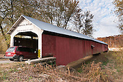 "Roseville Covered Bridge (263 feet long) was built in Burr Arch style over Big Raccoon Creek in 1910 by Van Fossen in Parke County, Indiana, USA. Red and white paint protects the wood. The ""Cross this bridge at a walk"" sign requires slow vehicle speed."