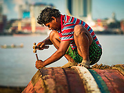 04 NOVEMBER 2015 - YANGON, MYANMAR: A worker repairs the hull of a small wooden ferry on the banks of the Yangon River in Dala, Yangon is in the background. Dala is located on the southern bank of Yangon River across from downtown Yangon, Myanmar. Many Burmese live in Dala and surrounding communities and go across the river into central Yangon for work. Before World War 2, the Irrawaddy Flotilla Company had its main shipyards in Dala. That tradition lives on in the small repair businesses the work on the hundreds of small wooden boats that serve as commuter ferries for the people of Yangon. The boats are pulled up onto the riverbank in Dala and repaired by hand.    PHOTO BY JACK KURTZ