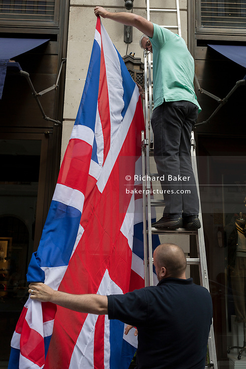 In the week of US President Donald Trump's state visit to the UK, employees check on which way up the British Union Jack flag should hang outside the American clothing retailer's Bond Street address, on 5th June 2019, in London, England.