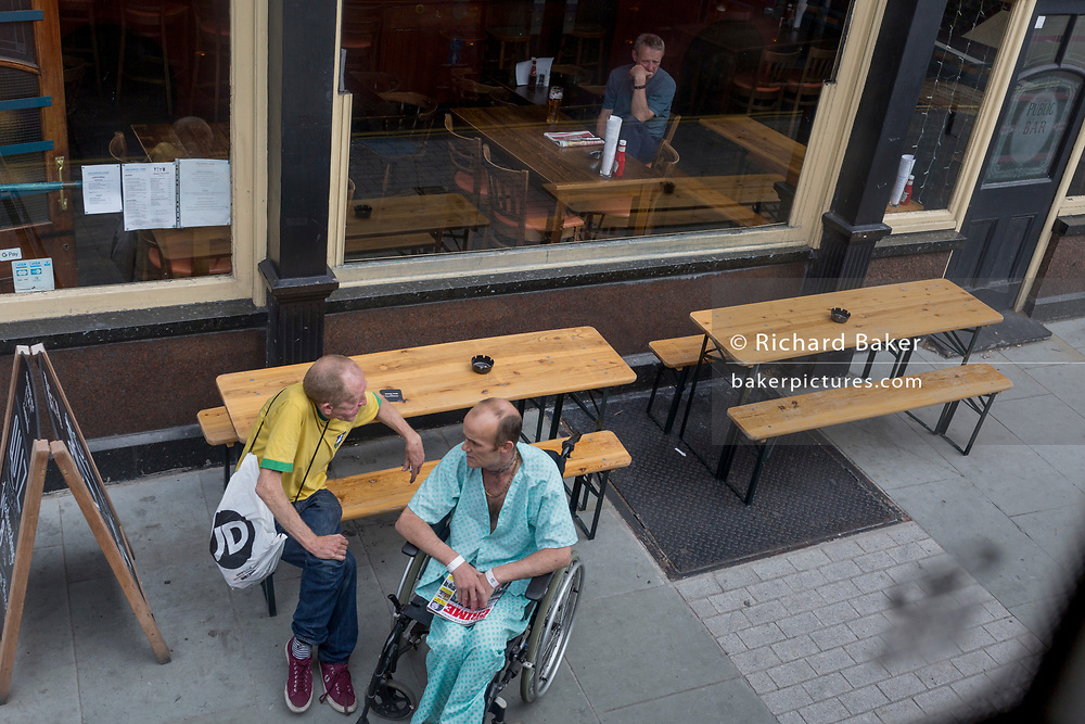 A hospital patient in a wheelchair and still wearing his ward scrubs sits outside a pub and talks with a friend in Camberwell, on 22nd August 2019, in London, England.