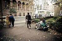 Friends embrace, a woman rests and a man strolls by in Astor Place, Manhattan, NY.