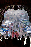 Silhouette of people entering archway at East entrance of Shwedagon Pagoda
