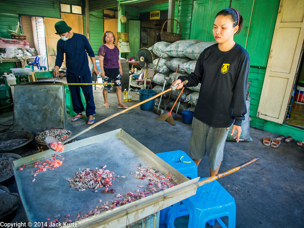 "28 OCTOBER 2014 - BANGKOK, THAILAND: A worker covers the lid of the oven in hot coals at the Pajonglak Maneeprasit Bakery in Bangkok. The cakes are called ""Kanom Farang Kudeejeen"" or ""Chinese Monk Candy."" The tradition of baking the cakes, about the size of a cupcake or muffin, started in Siam (now Thailand) in the 17th century AD when Portuguese Catholic priests accompanied Portuguese soldiers who assisted the Siamese in their wars with Burma. Several hundred Siamese (Thai) Buddhists converted to Catholicism and started baking the cakes. When the Siamese Empire in Ayutthaya was sacked by the Burmese the Portuguese and Thai Catholics fled to Thonburi, in what is now Bangkok. The Portuguese established a Catholic church near the new Siamese capital. Now just three families bake the cakes, using a recipe that is 400 years old and contains eggs, wheat flour, sugar, water and raisins. The same family has been baking the cakes at the Pajonglak Maneeprasit Bakery, near Santa Cruz Church, for more than 245 years. There are still a large number of Thai Catholics living in the neighborhood around the church.   PHOTO BY JACK KURTZ"