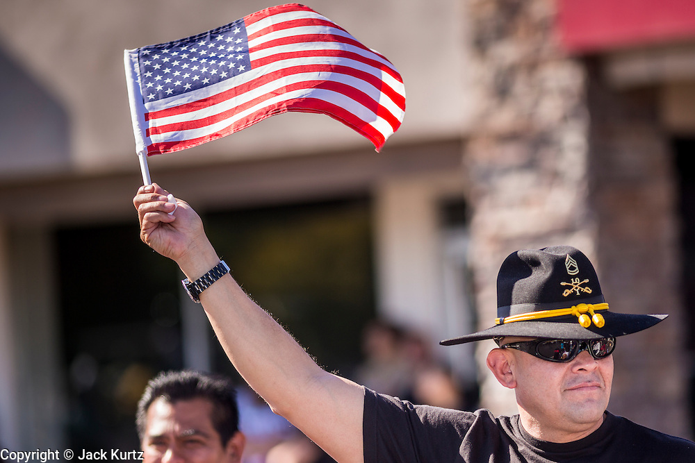 "11 NOVEMBER 2013 - PHOENIX, AZ: A veteran waves an American flag at the Phoenix Veterans Day Parade. The Phoenix Veterans Day Parade is one of the largest in the United States. Thousands of people line the 3.5 mile parade route and more than 85 units participate in the parade. The theme of this year's parade is ""saluting America's veterans.""    PHOTO BY JACK KURTZ"