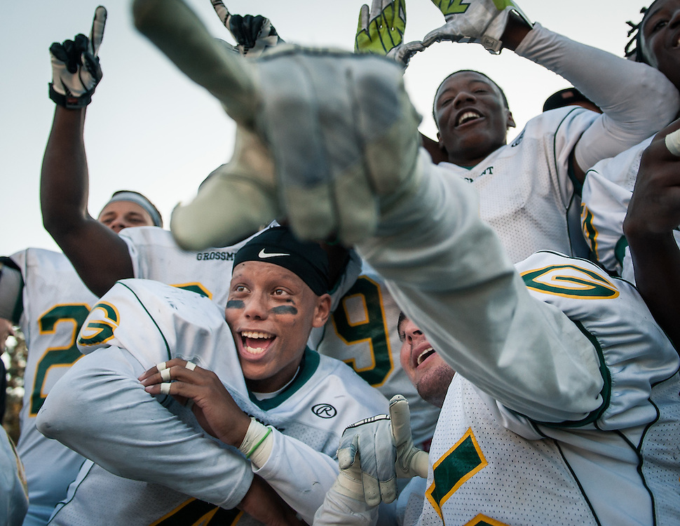 Grossmont College football players Brandon Payne (left), AJ Smith and Carnell Maurice (upper right) celebrate after their 30-23 victory over Santa Ana College on Nov 8th, 2014 in Santa Ana, CA.