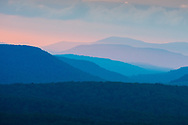 The distant mountain ridges appear to fan out from a single point like a hand holding a colorful deck of playing cards, the low sunlight giving each one a distinctive hue ascending from blue to pink.  Taken from Spruce Knob, West Virginia.