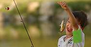 Five-year-old Dalton Frank proudly displays a fish he caught during the Sandhills Bass Masters Youth Fishing Derby Saturday, July 5, 2003, at the Carey Park Lagoon in Hutchinson, Kan. The club registered 154 youths ages 4 to 14 for the derby.