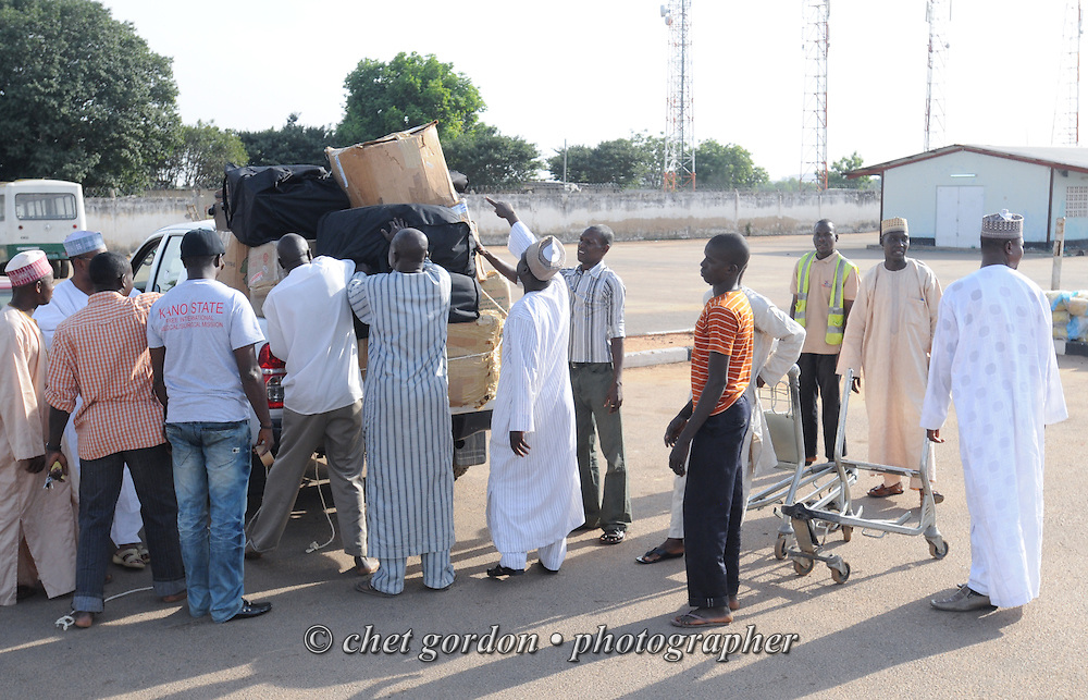 Nigerian men load cargo onto a pickup truck at Mallam Aminu Kano International Airport in Kano, Nigeria on Sunday, December 2, 2012.