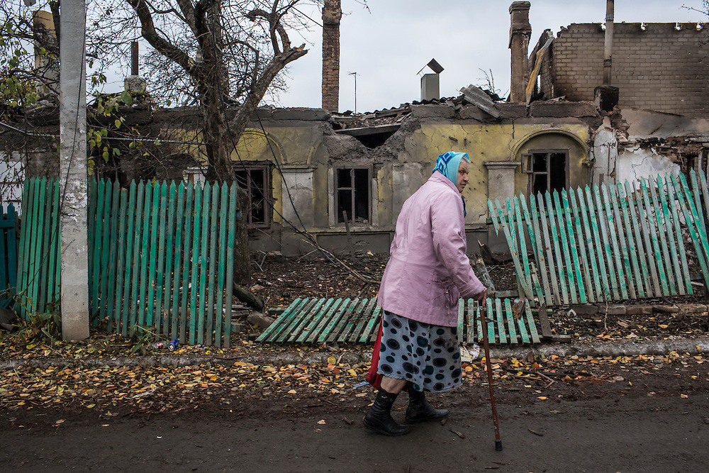 Nadezda Panasyk, 75, walks past a destroyed house in the Kievsky district where she lives on Friday, October 17, 2014 in Donetsk, Ukraine. Her apartment building is used by fighters for the Donetsk People's Republic to coordinate efforts to gain control of the Donetsk airport, one of the most heavily contested ongoing battles of the war in Eastern Ukraine. Photo by Brendan Hoffman, Freelance