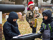 14 DECEMBER 2019 - DES MOINES, IOWA: HENRY WRIGHT, 11, plays the Star Spangled Banner on his saxophone during the ceremony to mark the laying of Christmas wreaths on veterans' graves. Volunteers working with Wreaths Across America placed Christmas wreaths on the headstones of more than 600 US military veterans in Woodland Cemetery in Des Moines. The cemetery, one of the first in Des Moines, has the graves of veterans going back to the War of 1812.    PHOTO BY JACK KURTZ