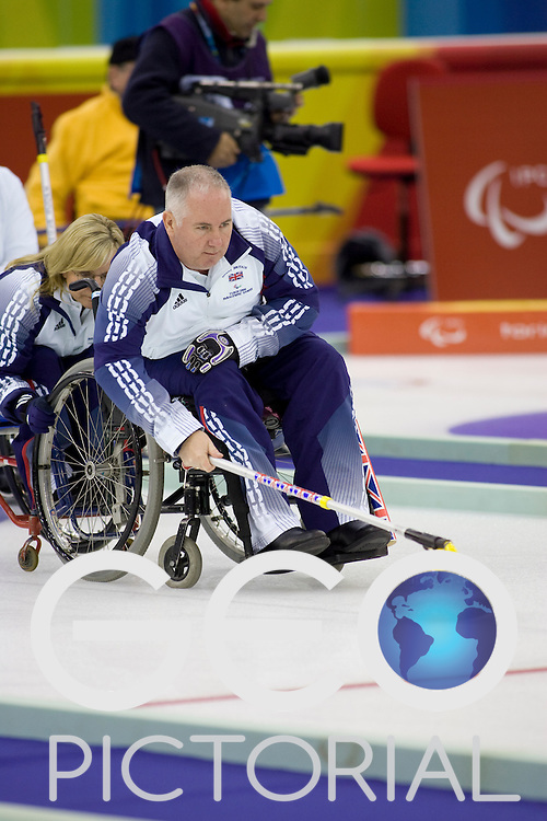 PINEROLO, ITALY - MARCH 15th : Held steady by team mate Angie Malone, team GBR skipper Frank Duffy lines up a stone during the last round-robin match of the curling competition between Great Britain and the USA during Day 5 of the Turin 2006 Winter Paralympic Games on March 15th, 2006 at the Pinerolo Palaghiaccio Stadium in Turin, Italy.