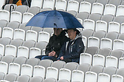 Spectators sheltering under an umbrella as the rain continues to fall during the International Test Match 2019 match between England and Australia at Lord's Cricket Ground, St John's Wood, United Kingdom on 14 August 2019.