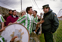 Podes, Asturias,Spain<br /> Football field in Podes, a small village in the north of Spain.A fan jokes with a police &copy; Carmen Secanella.